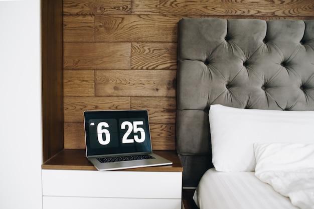 Laptop com relógio perto da cama, trabalhando em casa no início da manhã