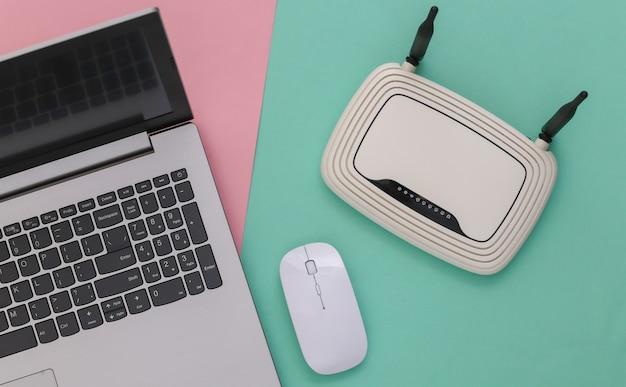 Laptop com roteador wi-fi em fundo rosa pastel azul. tiro do estúdio. vista do topo. postura plana
