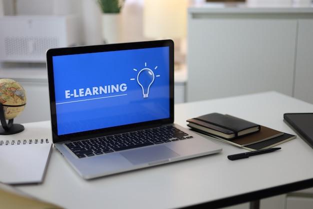 Laptop com simulação de tela em branco na mesa de madeira