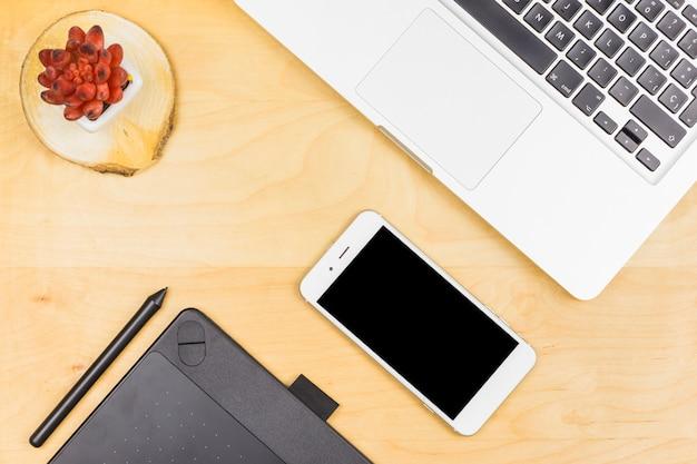 Laptop com smartphone e planta na mesa