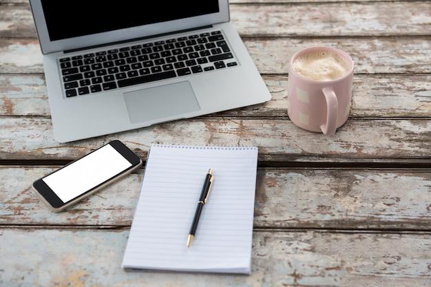 Laptop com smartphone e xícara de café