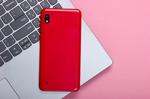 Laptop com smartphone em um pastel rosa