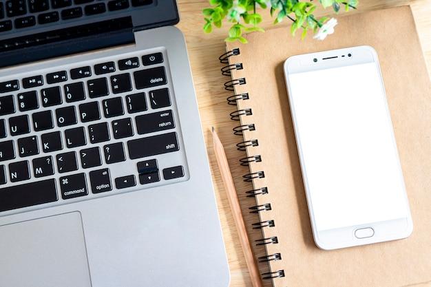 Laptop com smartphone no notebook, uma árvore de pote de lápis e flores sobre fundo de madeira, mesa de escritório vista superior.