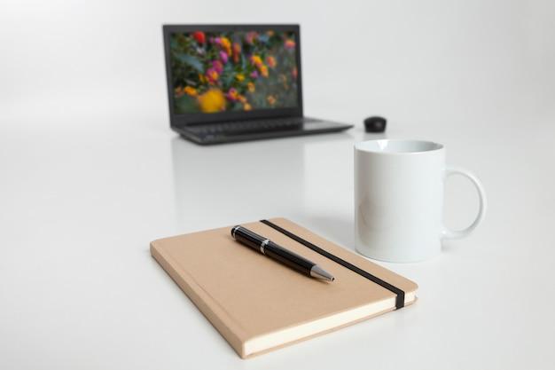 Laptop com tampa aberta, notebook e xícara de café em primeiro plano