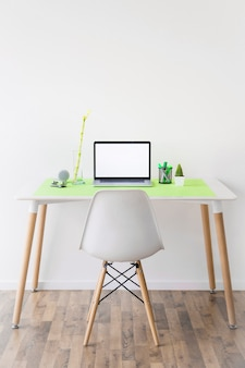 Laptop com tela branca em branco e marcadores no suporte na mesa