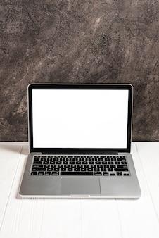 Laptop com tela branca em branco na mesa de madeira branca contra o concreto