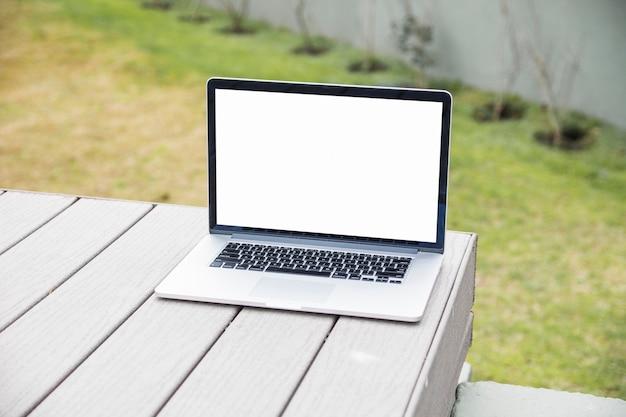 Laptop com tela branca em branco na mesa de madeira