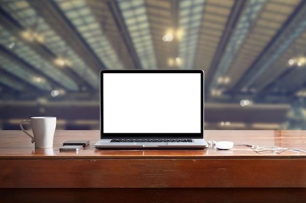 Laptop com tela branca em branco na mesa no fundo da fábrica