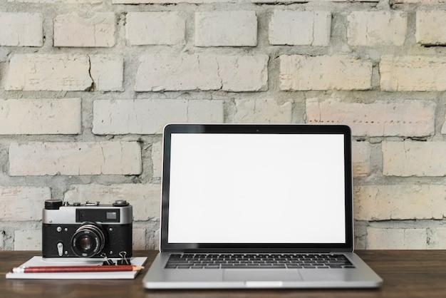 Laptop com tela branca em branco perto da câmera; bloco de anotações; lápis e buldogue na mesa de madeira