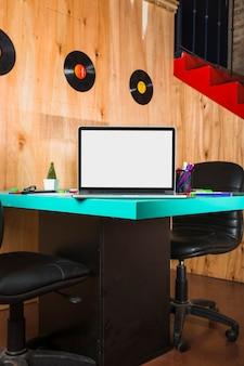 Laptop com tela branca em branco sobre uma mesa de madeira em um escritório