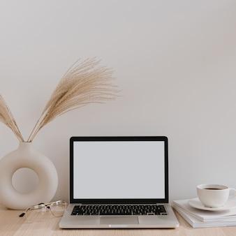 Laptop com tela de cópia em branco na mesa com buquê de grama de pampa em um vaso, copos, revistas e xícara de café