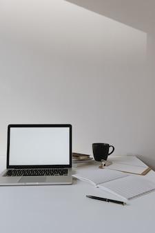 Laptop com tela de cópia em branco na mesa com xícara de café, folha de papel contra a parede branca