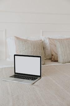 Laptop com tela de espaço de cópia em branco na cama com xadrez, almofadas contra a parede branca