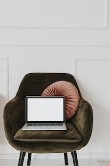 Laptop com tela de espaço de cópia em branco na poltrona com travesseiro contra a parede branca