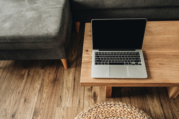 Laptop com tela de maquete em branco na mesa de madeira sólida.