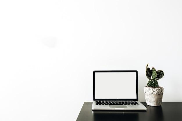 Laptop com tela de maquete vazia, suculenta na superfície branca.