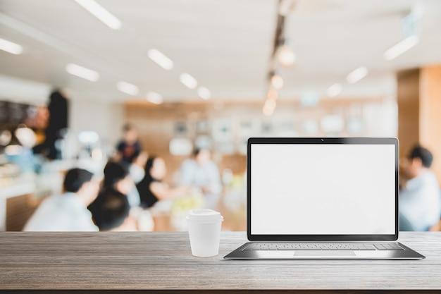 Laptop com tela em branco colocado na mesa turva reunião de pessoas