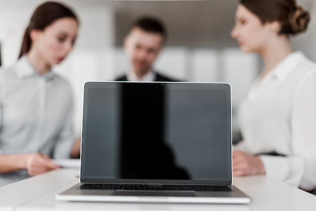 Laptop com tela em branco na frente do grupo de colegas de trabalho