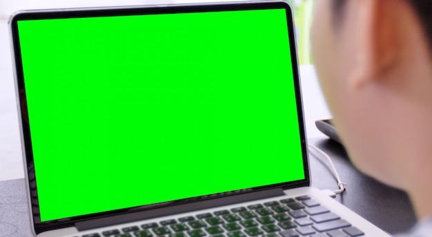 Laptop com tela verde para substituição com fundo desfocado