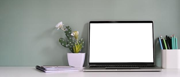 Laptop com uma tela branca em branco está colocando uma mesa de trabalho rodeada por vários equipamentos.