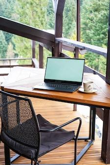 Laptop com uma xícara em uma mesa de madeira no terraço