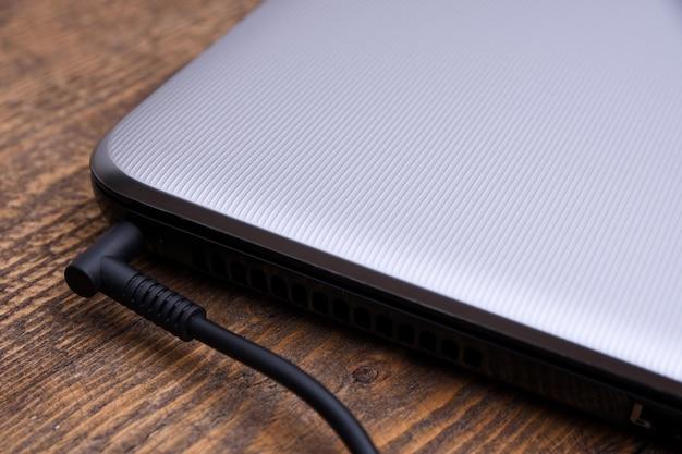 Laptop, computador está carregando de uma tomada de 220 volts em uma mesa perto da parede