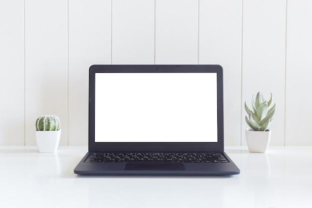 Laptop computador isolado tela branca com vaso de flores de cacto na mesa de madeira branca