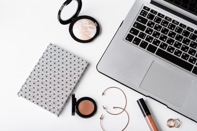 Laptop de cosméticos decorativos notebook e acessórios sobre a superfície branca