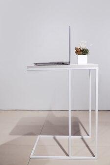 Laptop de estilo de vida minimalista em vista lateral da mesa de centro com espaço de cópia no fundo