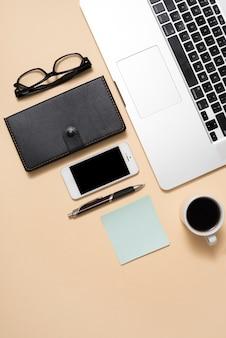 Laptop de imagem recortada com óculos; celular; xícara de café e diário sobre fundo bege