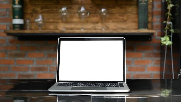 Laptop de maquete com tela em branco branca, colocando ao ar livre na mesa moderna com bar de cozinha clássica como