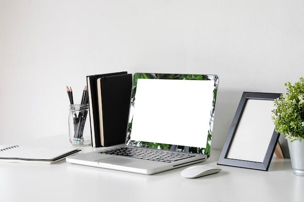 Laptop de maquete no espaço de trabalho com moldura, jarro de lápis, mouse na mesa do escritório.