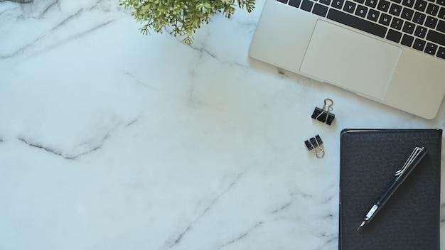 Laptop de mesa de escritório, caneta e caderno com planta na mesa de mármore com vista superior