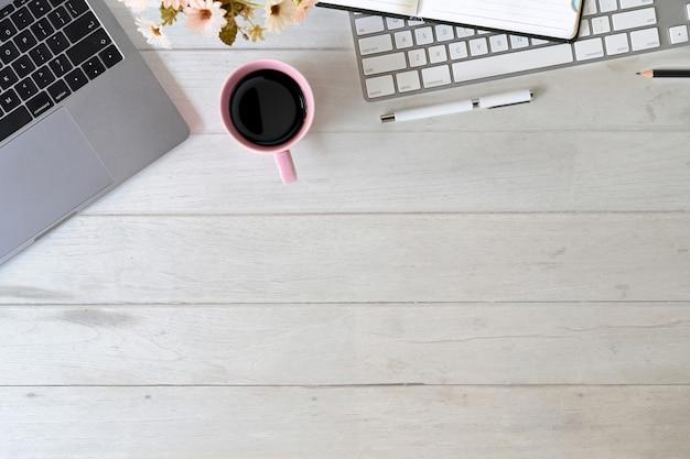 Laptop de mesa de escritório com teclado, caneca de café, notebook e material de escritório