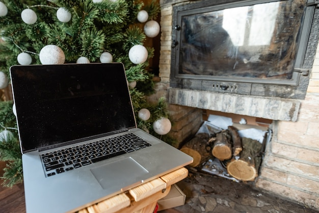 Laptop de natal com árvore de natal em uma velha casa de madeira