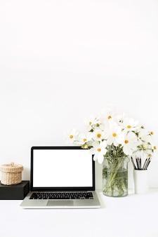 Laptop de pé na mesa branca contra uma parede branca com margaridas em um vaso, caixa preta, cesta de palha.