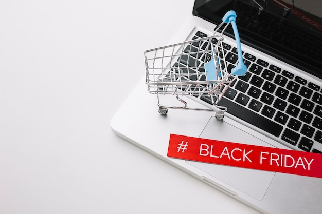 Laptop de sexta-feira preto e carrinho de compras com espaço de cópia