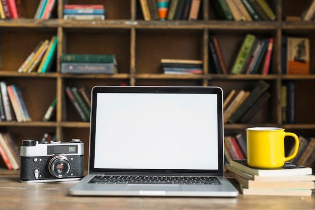 Laptop de tela em branco com câmera retro; caneca de café amarela; livro empilhado na mesa na sala da biblioteca