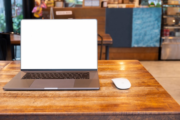 Laptop de tela em branco com o mouse na mesa no café.