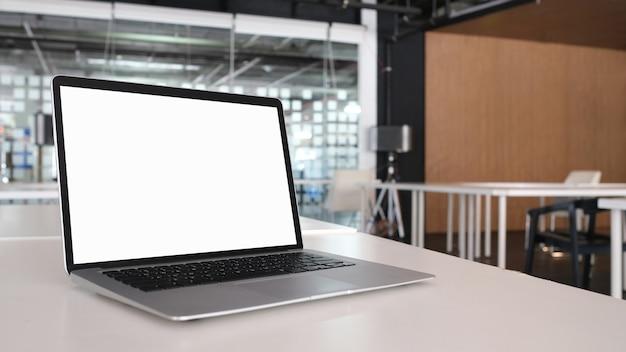 Laptop de tela em branco de imagem de maquete com branco para texto de publicidade na mesa branca.