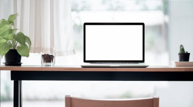 Laptop de tela em branco de maquete em mesa de balcão de madeira em co-espaço de trabalho