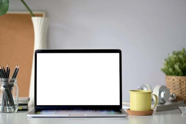 Laptop de tela em branco de maquete na mesa de madeira do espaço de trabalho