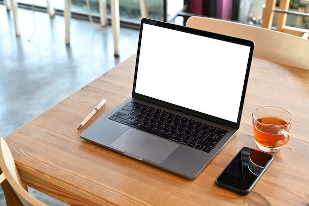 Laptop de tela em branco de maquete na mesa de madeira no café.