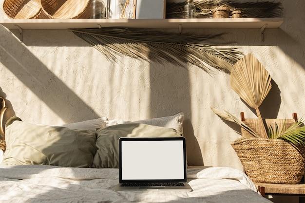 Laptop de tela em branco na cama com travesseiros e lençóis. design de interiores de casa de estilo boho com sombras de luz solar na parede.