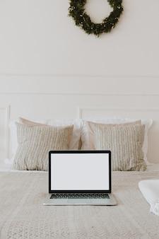 Laptop de tela em branco na cama com travesseiros e lençóis