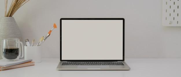 Laptop de tela em branco na mesa de escritório branca com pincel, xícara de café, agendar livros e decorações