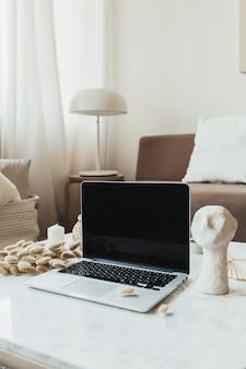 Laptop de tela em branco na mesa de mármore com busto e folhagem de junco