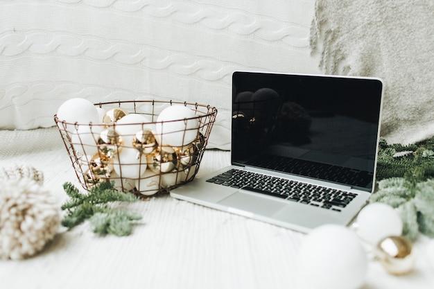 Laptop deitado sobre o cobertor branco decorado com galhos de árvores de natal e uma cesta festiva de bolas brancas e douradas