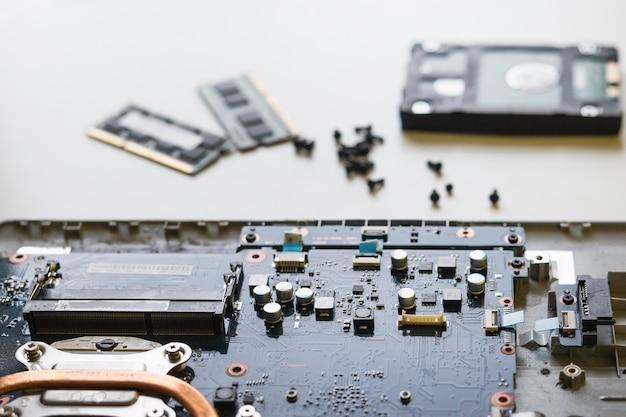 Laptop desmontando peças e dispositivos na parede branca, conserto de laptop