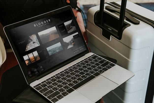 Laptop do blogger perto de uma bagagem no aeroporto